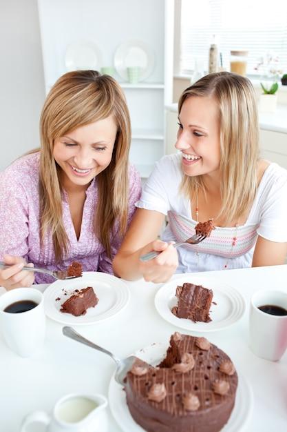 Amigas alegres comendo um bolo de chocolate na cozinha Foto Premium