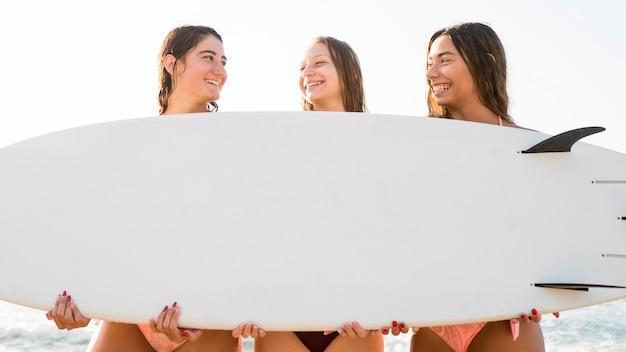 Amigas de tiro médio segurando uma prancha de surf Foto gratuita