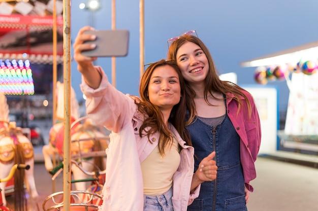 Amigas no parque de diversões tirando uma selfie Foto gratuita