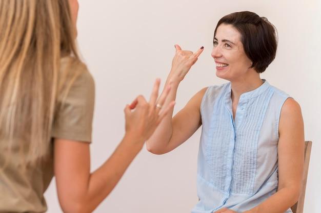 Amigas usando linguagem de sinais para falar umas com as outras Foto Premium