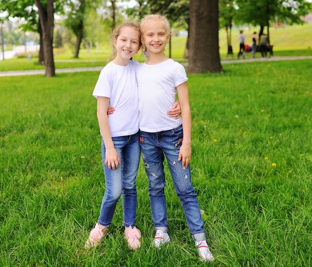 Amigo de menina das crianças pequenas que sorri, hortaliças no parque. Foto Premium