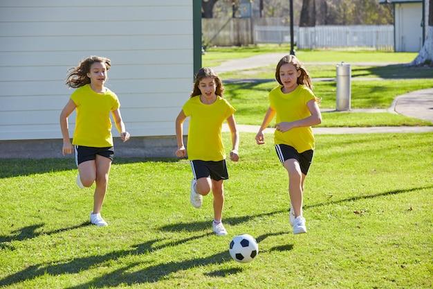 Amigo meninas adolescentes jogando futebol futebol em um parque Foto Premium