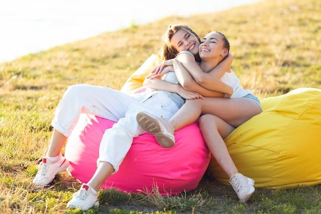 Amigos, abraçando, ligado, beanbag Foto gratuita