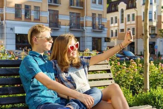 Amigos adolescentes menina e menino sentado no banco na cidade, falando Foto Premium