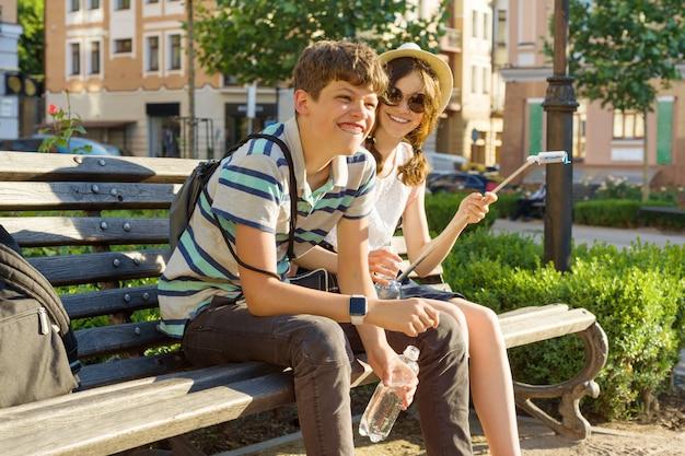 Amigos adolescentes menina e menino sentado no banco na cidade, sorrindo, conversando Foto Premium