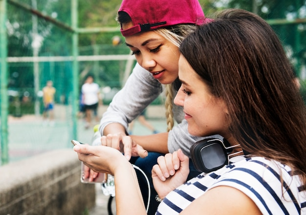 Amigos adultos jovens do sexo feminino ouvindo música através de seu smartphone ao ar livre Foto Premium