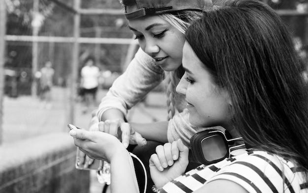 Amigos adultos jovens do sexo feminino ouvindo música através de seu smartphone ao ar livre Foto gratuita