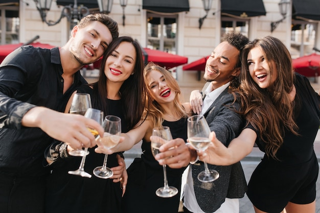 Amigos alegres bebendo champanhe em festa ao ar livre Foto gratuita