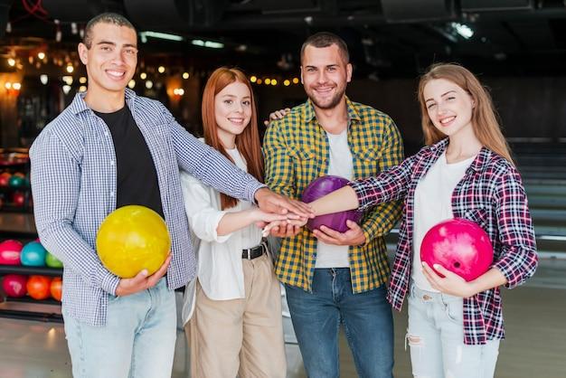 Amigos alegres com bolas de boliche em um clube de boliche Foto gratuita