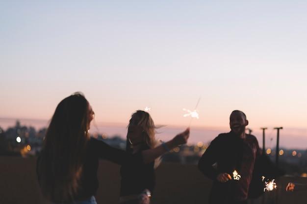 Amigos alegres com estrelinhas à noite Foto gratuita