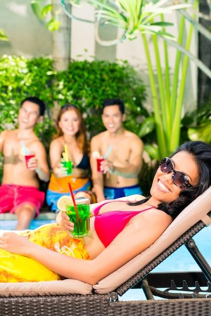 Amigos asiáticos festejando na festa da piscina no resort Foto Premium