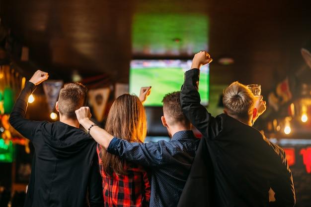 Amigos assistem futebol na tv em um bar esportivo Foto Premium