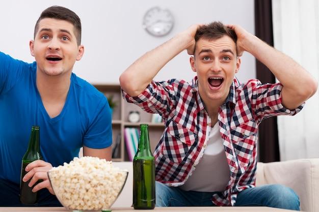 Amigos assistindo esportes na tv Foto gratuita
