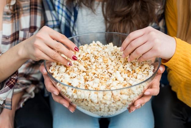 Amigos assistindo um filme enquanto come pipoca Foto gratuita