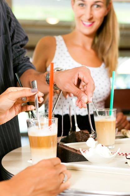 Amigos, bebendo café com leite e comendo bolo Foto Premium