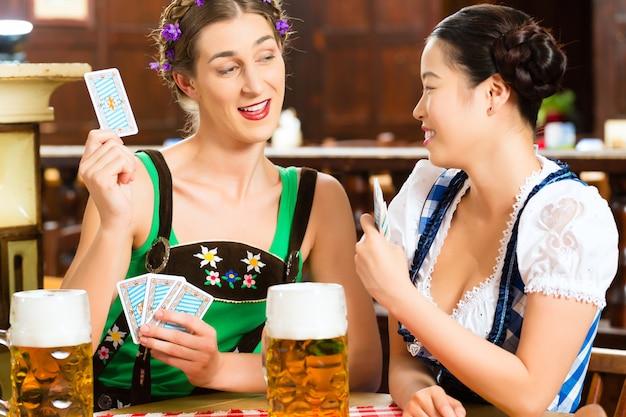 Amigos, bebendo cerveja, em, bavarian, barzinhos, cartas de jogar Foto Premium