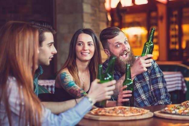 Amigos, bebendo e comendo pizzas em um bar Foto Premium