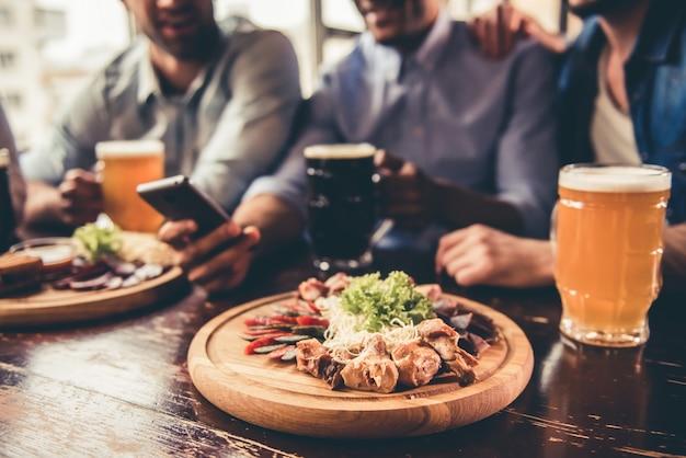 Amigos bonitos estão bebendo cerveja, usando telefone inteligente. Foto Premium