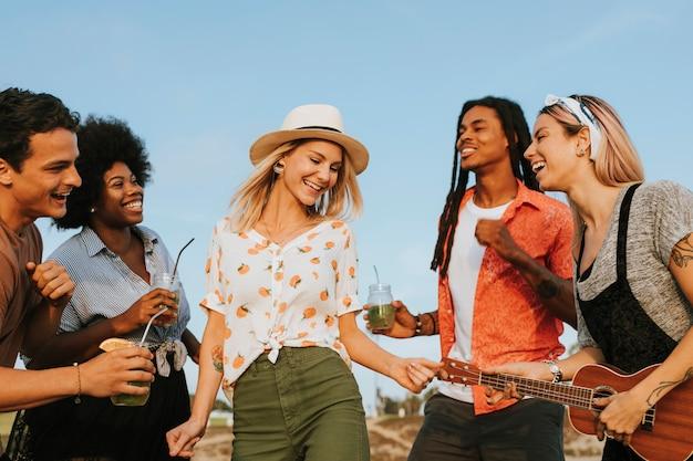 Amigos cantando e dançando na praia Foto Premium