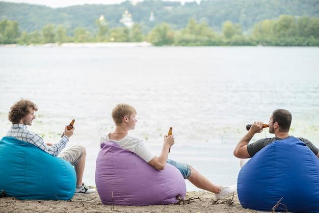 Amigos, com, cerveja, relaxante, perto, água Foto gratuita