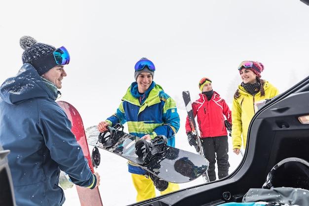 Amigos, com, esqui, e, placa neve, descarregando, material, de, a, car Foto Premium