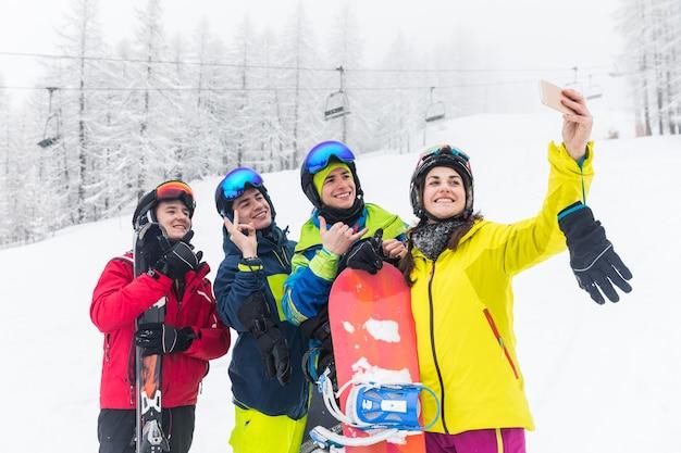 Amigos, com, esqui, e, snowboard, levando, um, selfie, ligado, a, declives Foto Premium