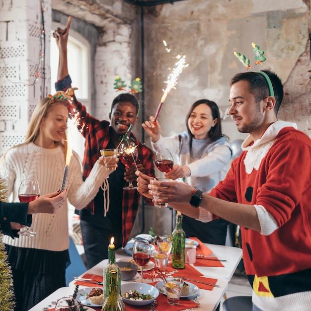 Amigos com fogos de artifício nas mãos. grupo de amigos comemorando a véspera de ano novo juntos. Foto Premium