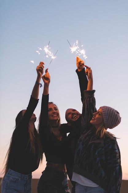Amigos, com, sparklers, em, noite Foto gratuita