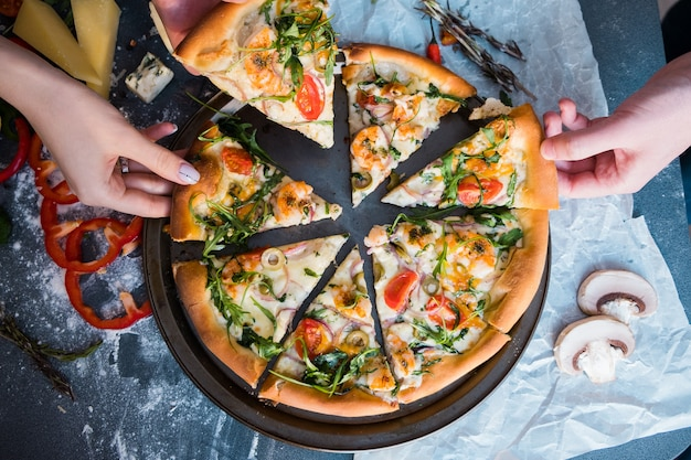 Amigos comendo pizza. mãos do povo, pegando uma fatia de pizza Foto Premium