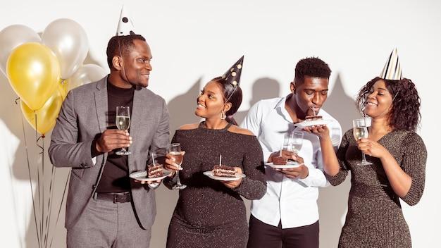 Amigos comendo um bolo delicioso vista frontal Foto gratuita