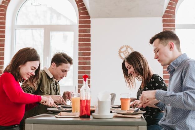 Amigos, comer, em, um, restaurante Foto gratuita