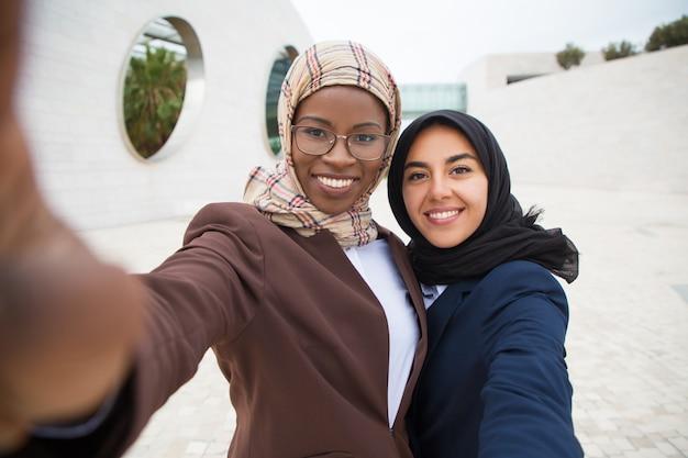 Amigos corporativos femininos alegres tomando selfie Foto gratuita