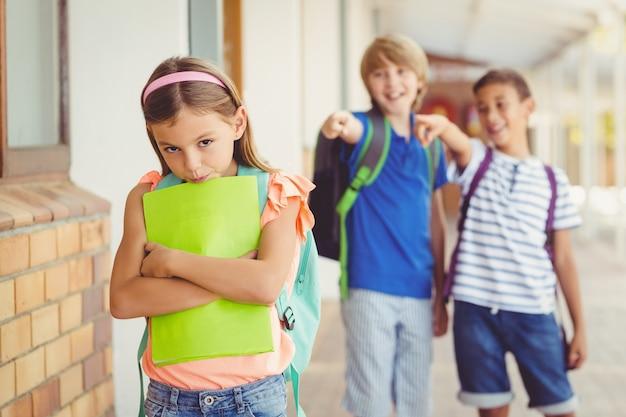 Amigos da escola bullying uma menina triste no corredor Foto Premium