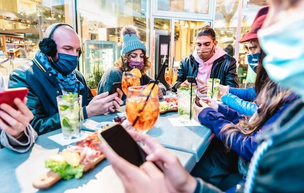 Amigos da geração do milênio usando smartphones em um bar de coquetéis Foto Premium
