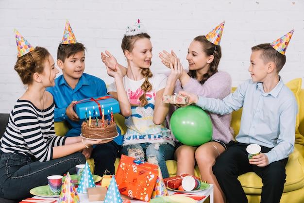 Amigos dando o bolo de aniversário e presentes para seu amigo na festa Foto gratuita