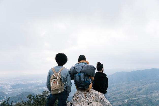 Amigos de alpinista bem sucedidos apreciar a vista no pico da montanha Foto gratuita