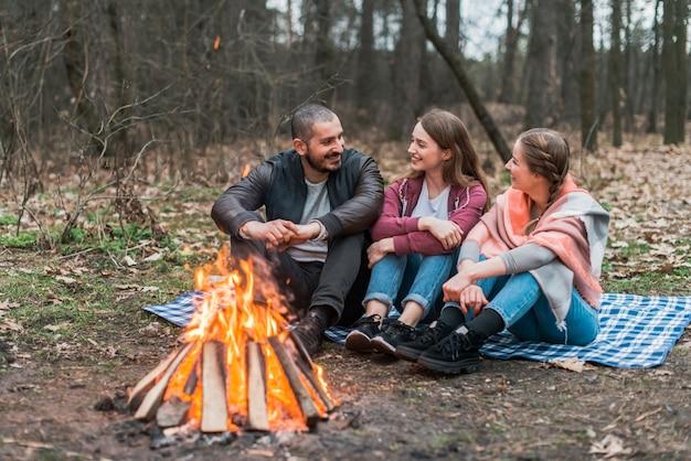 Amigos de alto ângulo conversando na fogueira Foto gratuita