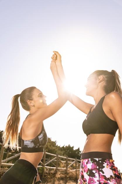 Amigos de baixo ângulo desportivo fazendo um high five Foto gratuita