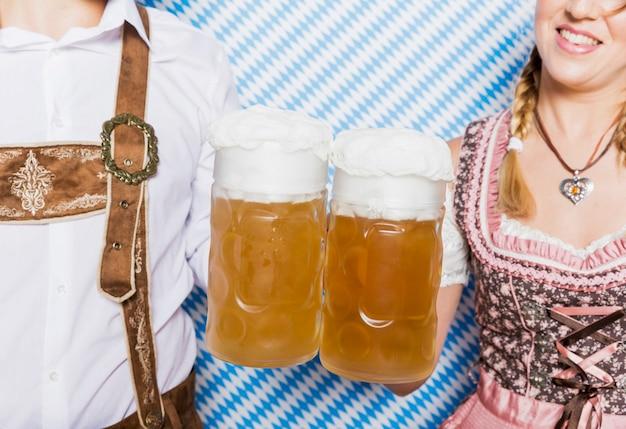 Amigos de close-up segurando canecas de cerveja Foto gratuita
