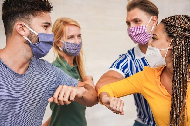 Amigos de jovens batem os cotovelos em vez de cumprimentar com um olhar de abraço Foto Premium