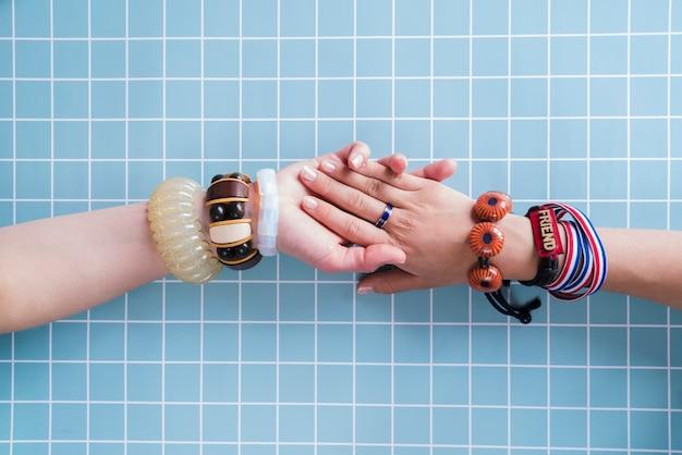 Amigos de mãos dadas com pulseiras Foto gratuita