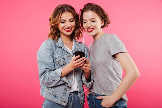 Amigos de mulheres alegres, usando música do telefone móvel. Foto gratuita