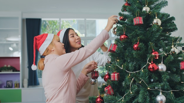 Amigos de mulheres asiáticas decoram a árvore de natal no festival de natal. o sorriso feliz adolescente fêmea comemora férias de inverno do xmas junto na sala de visitas em casa. Foto gratuita