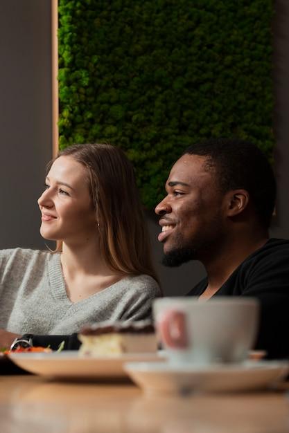 Amigos de vista lateral no restaurante Foto gratuita