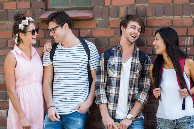 Amigos do quadril encostado na parede e rindo Foto Premium