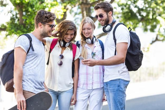 Amigos do quadril olhando para smartphone ao ar livre Foto Premium