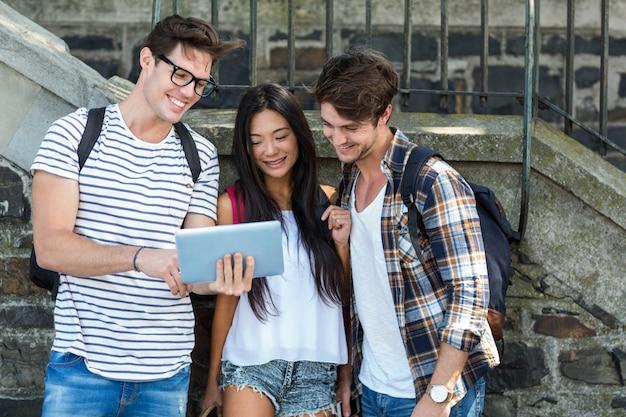 Amigos do quadril olhando para tablet na rua Foto Premium