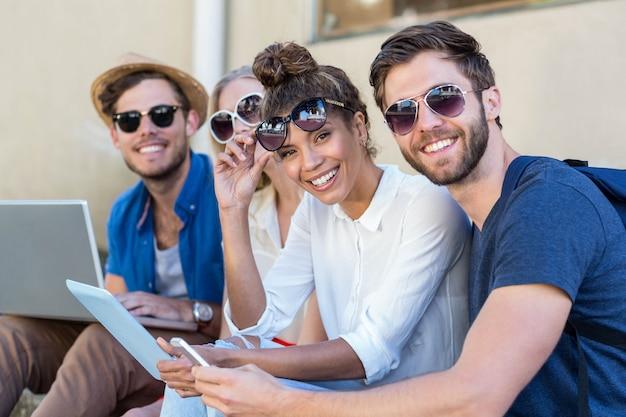 Amigos do quadril sentado na calçada e usando o laptop, tablet e smartphone Foto Premium