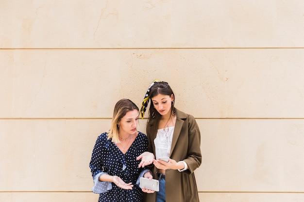 Amigos do sexo feminino chateados em frente a parede olhando para celular Foto gratuita