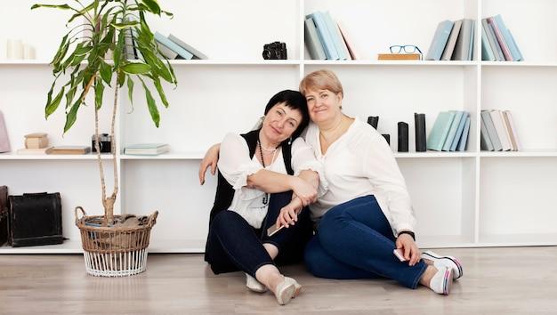 Amigos do sexo feminino em um estúdio com livros Foto gratuita